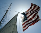 stock photo of tall ship  - An Amrican Flag on a Sailing Ship Billows in the Wind - JPG