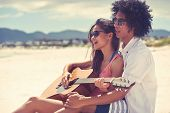 pic of couple sitting beach  - Cute hispanic couple playing guitar serenading on beach in love and embrace - JPG