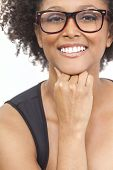 stock photo of geek  - A beautiful intelligent mixed race African American girl or young woman looking happy and wearing geek glasses - JPG