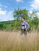 stock photo of lederhosen  - Young man in traditional Bavarian lederhosen walking alone in the field - JPG