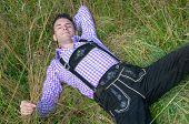 pic of lederhosen  - Young man in traditional Bavarian lederhosen relaxing in the field - JPG
