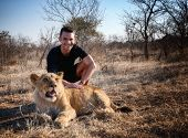 Caucasian man posing with lion in Zimbabwe, Africa