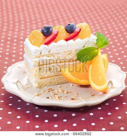 delicious cake topping with fresh orange strawberry and blueberry