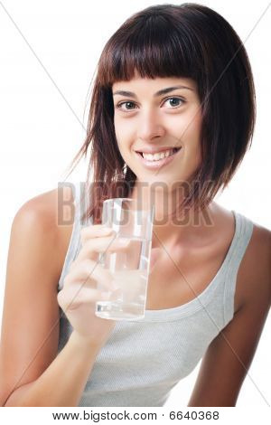 Beautiful smiling young woman holding a glass of water