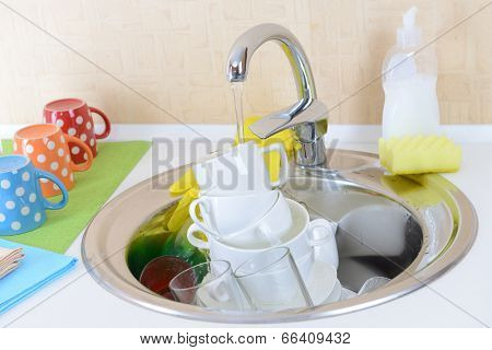 Stack of dishes soaking in kitchen sink