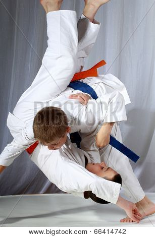 Sportsman in judogi and with blue belt is doing throw