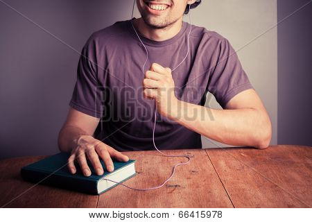 Young Man Listening To Audio Book