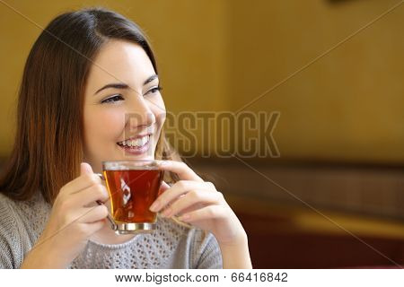 Happy Woman Thinking Holding A Cup Of Tea In A Coffee Shop
