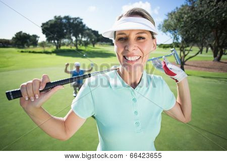 Lady golfer smiling at camera with partner cheering behind on a sunny day at the golf course