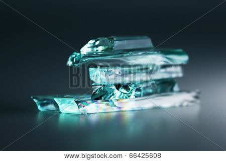 Small pieces of broken or shattered glass stacked,with dark background.