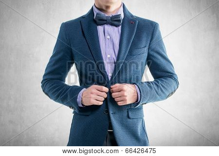 Handsome elegant young fashion man in coat tuxedo classical costume suit and bow tie
