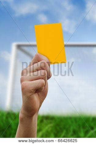 Hand holding up yellow card against goalpost on grass under blue sky