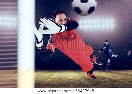 Fit goal keeper jumping up against football pitch under spotlights