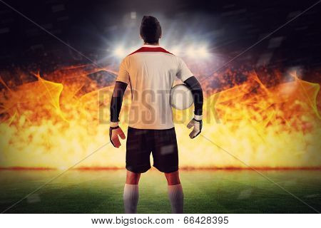 Goalkeeper standing in white jersey against football pitch under spotlights