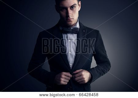 Portrait of  attractive handsome stylish fashion young man in elegant casual classical suit with bow