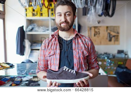 Portrait of a handsome man selling footwear in sports shop