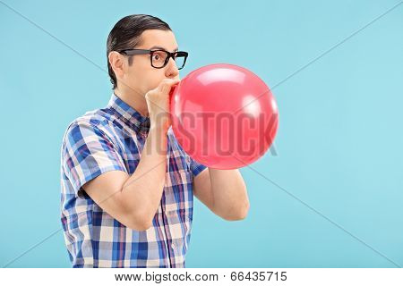 Man with glasses blowing up a balloon on blue background
