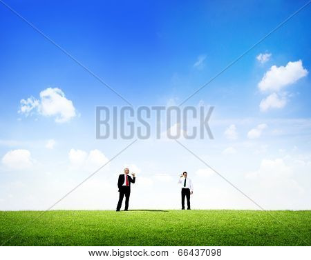 Two business men standing in outdoors talking through tin can phone.