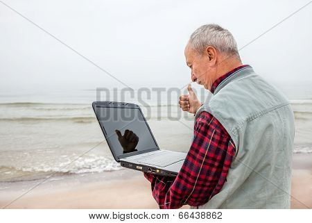 Old Man Standing On The Beach With A Laptop
