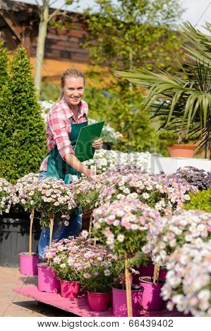 Happy woman make inventory potted flowers at garden shopping center