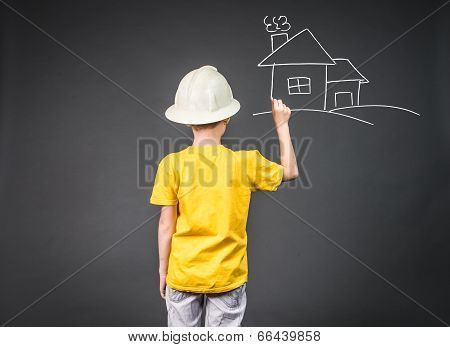 Cute boy in in helmet chalk his home. Family house concept - portrait of lovely boy with a house. Co