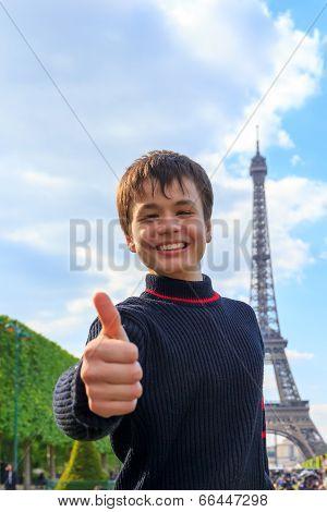 Cheerful Teenager Shows Thumb Up Near Eiffel Tower (la Tour Eiffel)