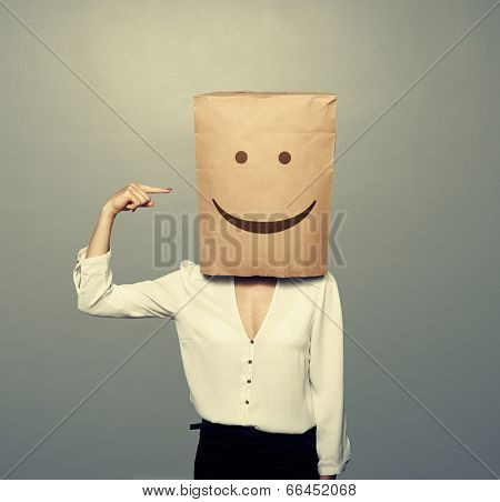 woman with paper bag on the head pointing at smile over white background