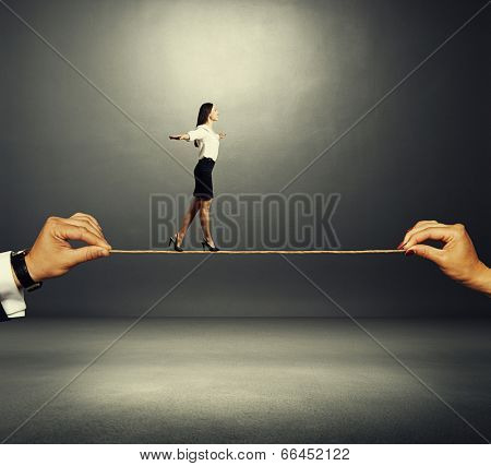assured smiley woman walking on the rope over dark background