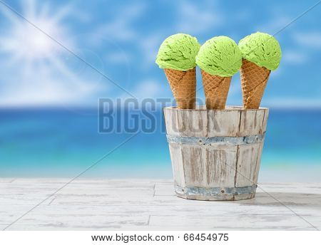 Mint ice creams in rustic wooden bucket at the beach with sun flare