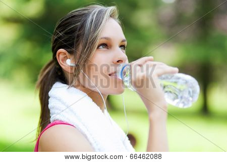 Woman refreshing after running at the city park