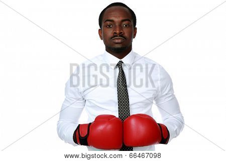 Portrait of a serious african businessman wearing boxing gloves over white background
