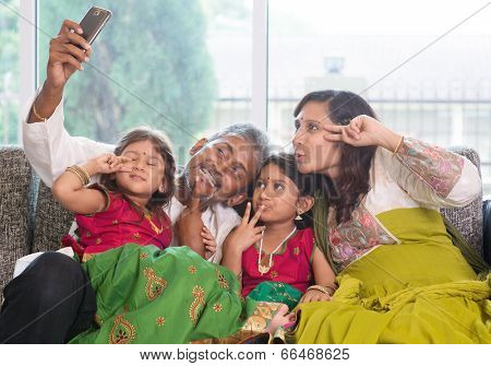 Asian Indian family selfie or self photograph at home. Parents and children indoor lifestyle.