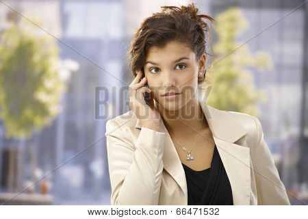 Outdoor portrait of pretty businesswoman talking on mobilephone.