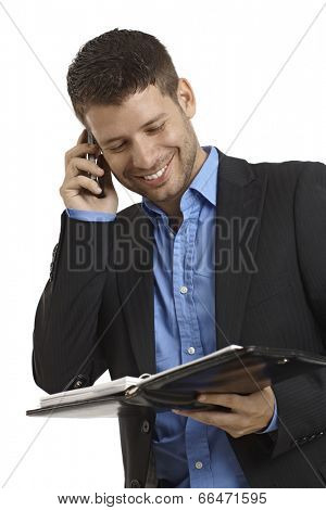 Happy young businessman talking on mobilephone, holding organizer.