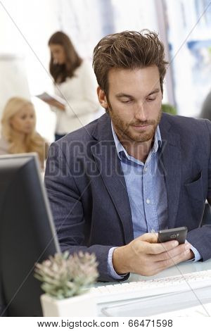 Young businessman sitting at desk in office, using mobilephone.