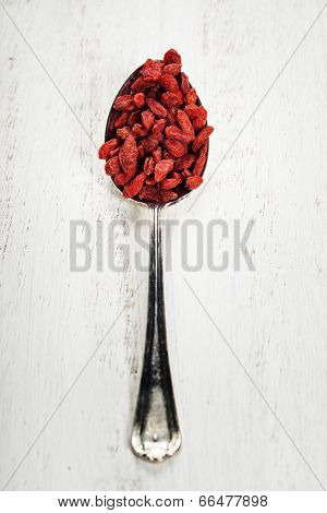 Metal tablespoon of dried goji berries on wooden background
