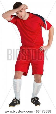 Football player in red wiping his brow on white background