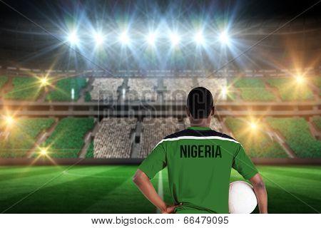 Nigeria football player holding ball against stadium full of nigeria football fans