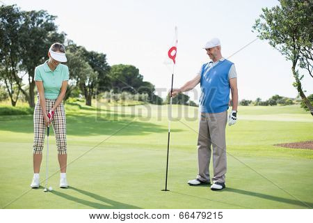 Golfing couple at the eighteenth hole on the golf course on a sunny day at the golf course