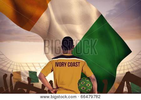 Ivory coast football player holding ball against large football stadium under cloudy blue sky