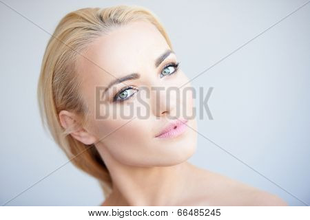 Beautiful serene young blond woman tilting her head quizzically as she looks at the camera with a serious expression  head portrait on grey