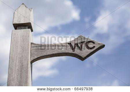 Old wooden signpost over blue sky background.