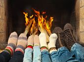 stock photo of brother sister  - Feets of a family wearing woolen socks warming near the fireplace - JPG