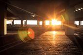 image of peek  - Sun peeking into large dark empty grunge parking structure interior - JPG
