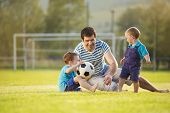 foto of football pitch  - Young father with his little sons playing football on football pitch - JPG