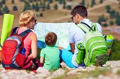 stock photo of family planning  - happy family in mountains discussing the route - JPG