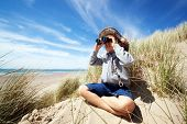 stock photo of safari hat  - Little boy searching with binoculars at the beach dressed as explorer concept for nature - JPG