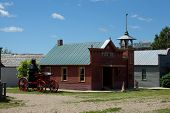 stock photo of firehouse  - The side view of a historic firehouse with a fire wagon - JPG