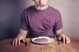 stock photo of table manners  - A young man is sitting at a table and eating a purple jelly pudding - JPG