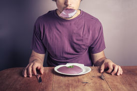 picture of table manners  - A young man is sitting at a table and eating a purple jelly pudding - JPG